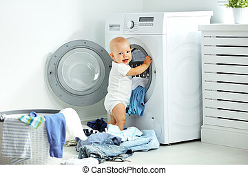 happy baby boy to wash clothes and laughs in laundry