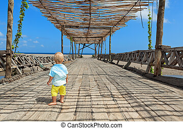 Happy baby boy walk by wood bridge to ocean beach
