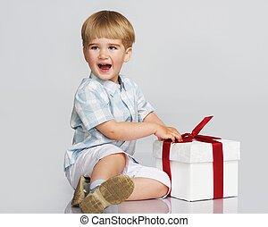 Happy baby boy with a gift box