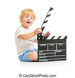 Happy baby boy with clapper board sitting on floor