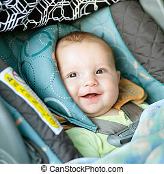 Happy baby buckled into rear-facing car seat