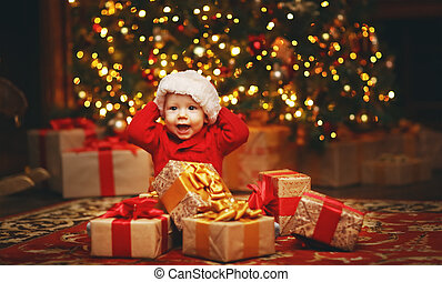Happy baby by Christmas tree with gifts