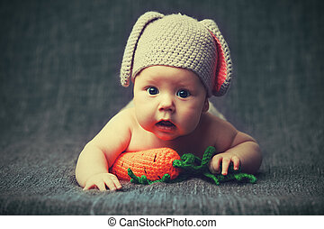 happy baby child in costume a rabbit bunny with carrot on a grey