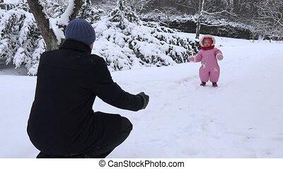 Happy baby child walk toward father on snow in winter season. 4K
