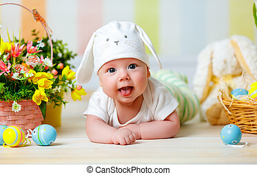 happy baby child with Easter bunny ears and eggs and flowers...