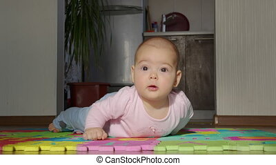 Happy baby crawls in the room. Infant baby plays with family in the house