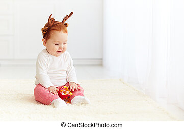 happy baby deer playing with toy at home