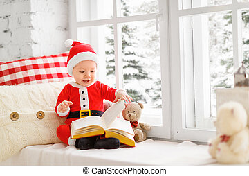 happy baby dressed as Santa Claus sitting on window of house in winter
