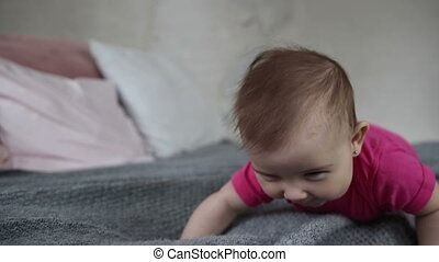 Happy baby girl crawling on bed - Portrait of laughing...