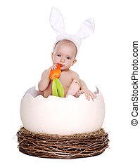 happy baby girl easter rabbit sitting in a giant easter egg eating carrot