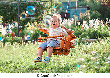 Happy baby girl having fun on a swing. Sunny playground in a kindergarten. Sunny playground in the back yard. The concept of the International Children's Day