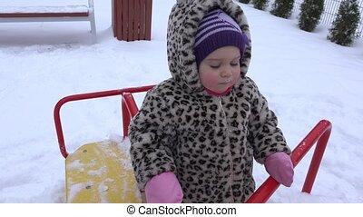 Happy baby girl having fun on swing ride at winter playground. 4K