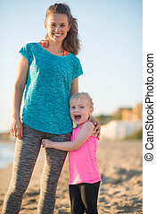 Happy baby girl hugging mother on beach in the evening