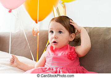 happy baby girl in crown on birthday party at home