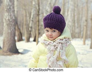 Happy baby girl in hat outdoor winter background