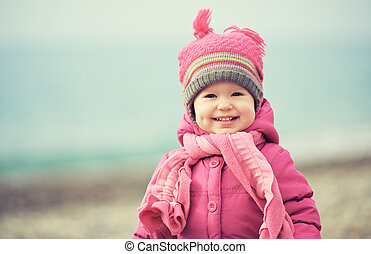 Happy baby girl in pink hat and scarf laughs - Happy baby...