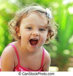 Happy baby girl joy with opened mouth outdoor summer...