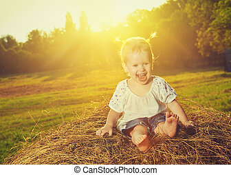 happy baby girl laughing on hay in summer
