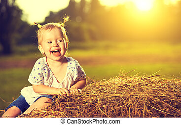 happy baby girl laughing on hay in summer at sunset