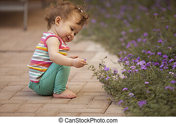 Happy baby girl picking flowers