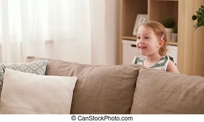 happy baby girl playing hide and seek game at home -...