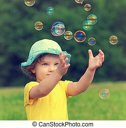 Happy baby girl playing with bubbles the hands on summer...