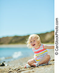 Happy baby girl playing with sand on beach