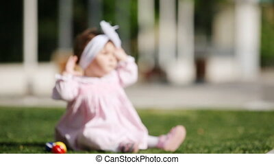 Happy baby-girl seated on the green grass in the park and playing, blured image.