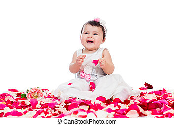 happy baby girl sitting among rose petals