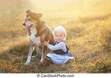 Happy Baby Girl Sitting in Field With Adopted German Shepherd Pet Dog