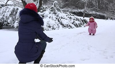 Happy baby girl walk toward mother on snow in winter season. 4K
