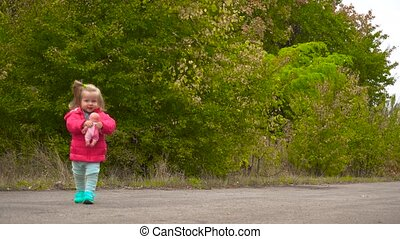 Happy baby girl walking in autumn park and holding doll in...
