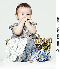 Happy baby girl with flowers. Cute little child