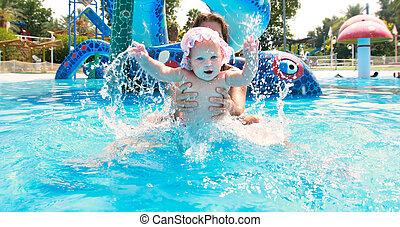 happy baby girl with mother in waterpool