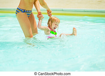 Happy baby girl with mother playing in swimming pool
