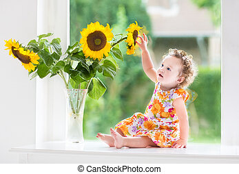 Happy baby girl with sunflowers