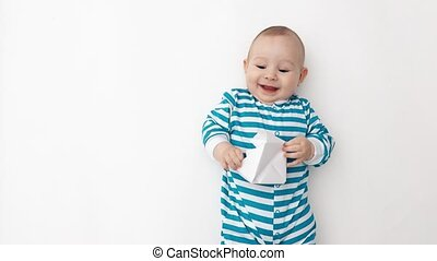 Happy baby holding paper boat - Baby wearing striped romper...