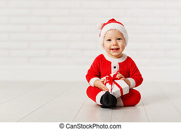Happy baby in a Christmas costume Santa Claus with gifts