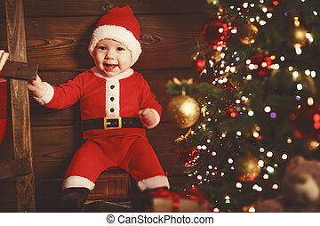 Happy baby in a Christmas costume Santa Claus at christmas tree