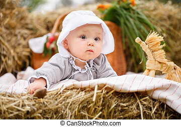 Happy baby in a field with hay rolls at sunset.