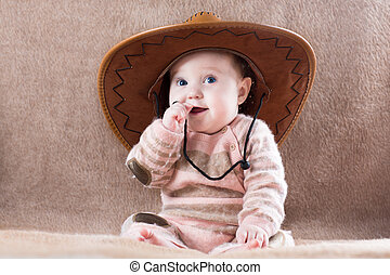 Happy baby in cow girl with big hat