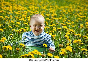 happy baby in flowers meadow