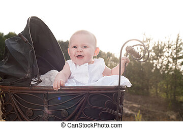 Happy baby in her pram - Baby girl is sitting in a vintage...
