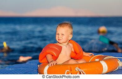 Happy baby in life-buoy on the pontoon