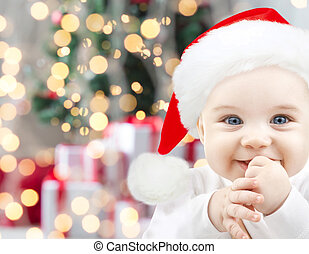 happy baby in santa hat over christmas lights