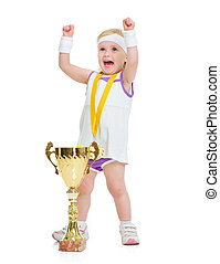Happy baby in tennis clothes with medal and goblet rejoicing success