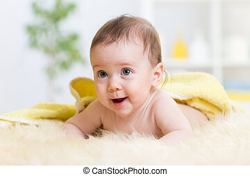 Happy baby in towel crawling on floor at home