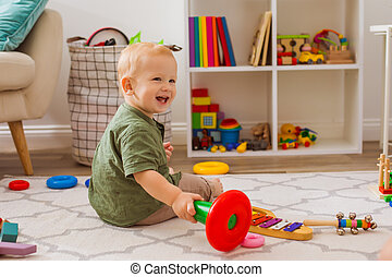 Happy baby is playing with different toys in the nursery
