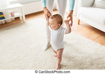 happy baby learning to walk with mother help - family,...