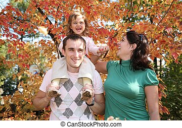 happy baby on father`s shoulders with mother in the park